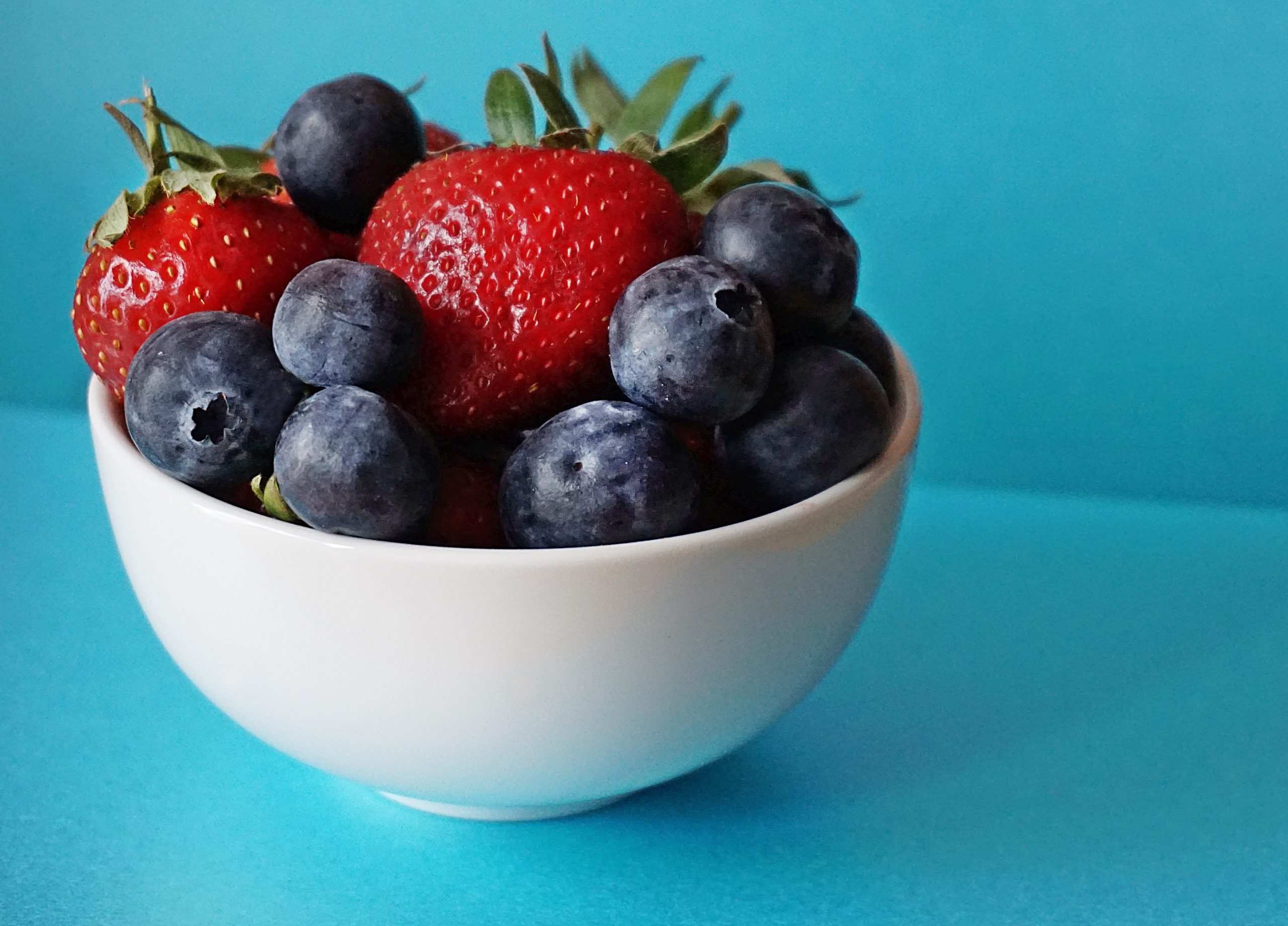 blueberries and strawberries in white ceramic bowl 1120575 scaled